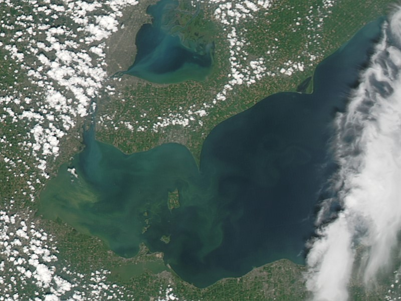 An August 2014 NASA satellite image of the western end of Lake Erie shows milky-green phytoplankton and algae blooms in the coastal waters of Ohio, Michigan, and southwestern Ontario. Such blooms are largely caused by nutrients running off farmlands and can lead to issues such as water-supply shutdowns. This part of the Great Lakes is a study area for the Coastal Observations, Mechanisms, and Predictions Across Systems and Scales (COMPASS) project.